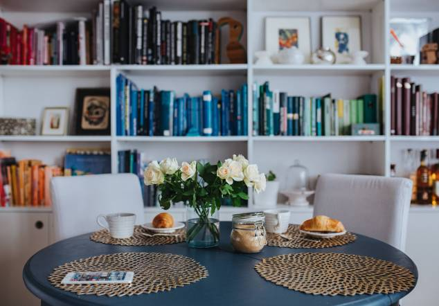 kaboompics_Round breakfast table with white flowers by the bookcase