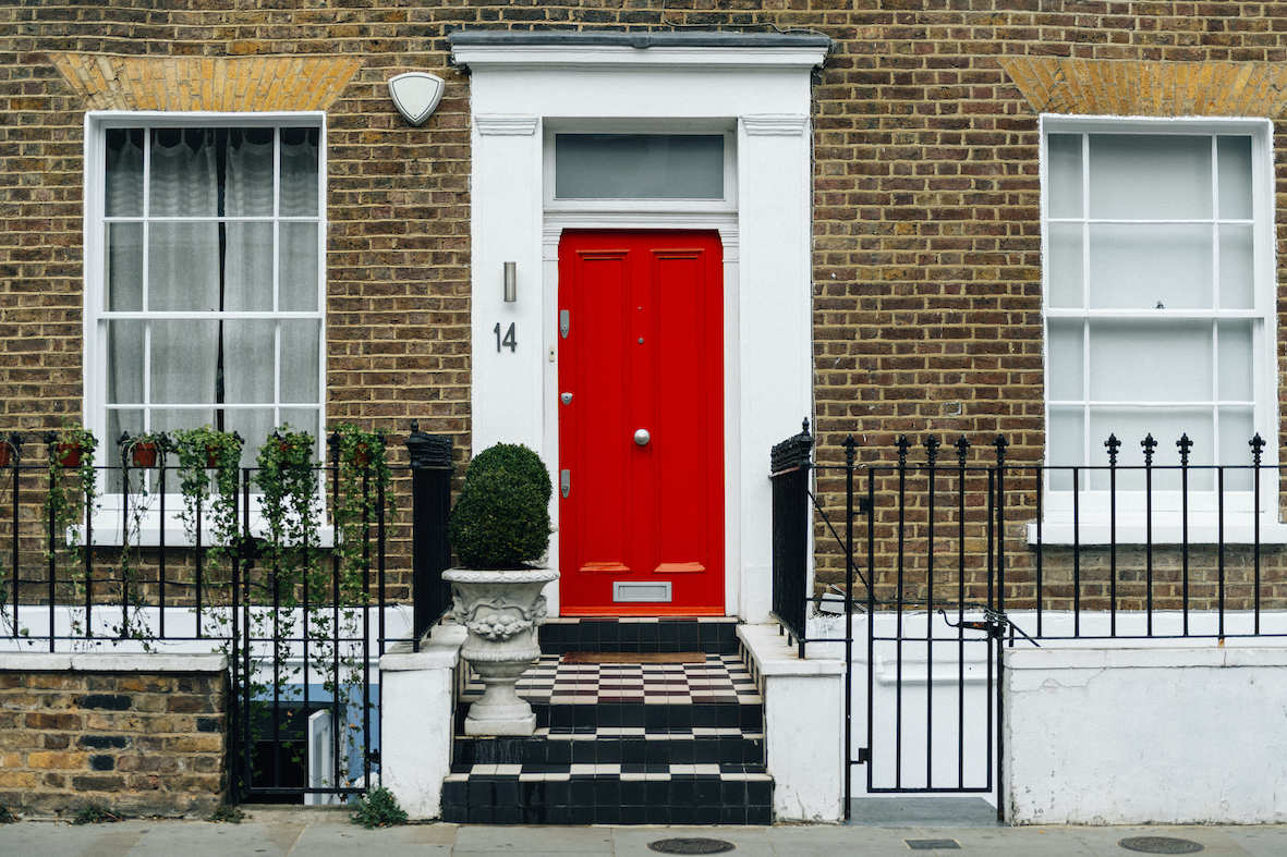 Red colored front door of a city house