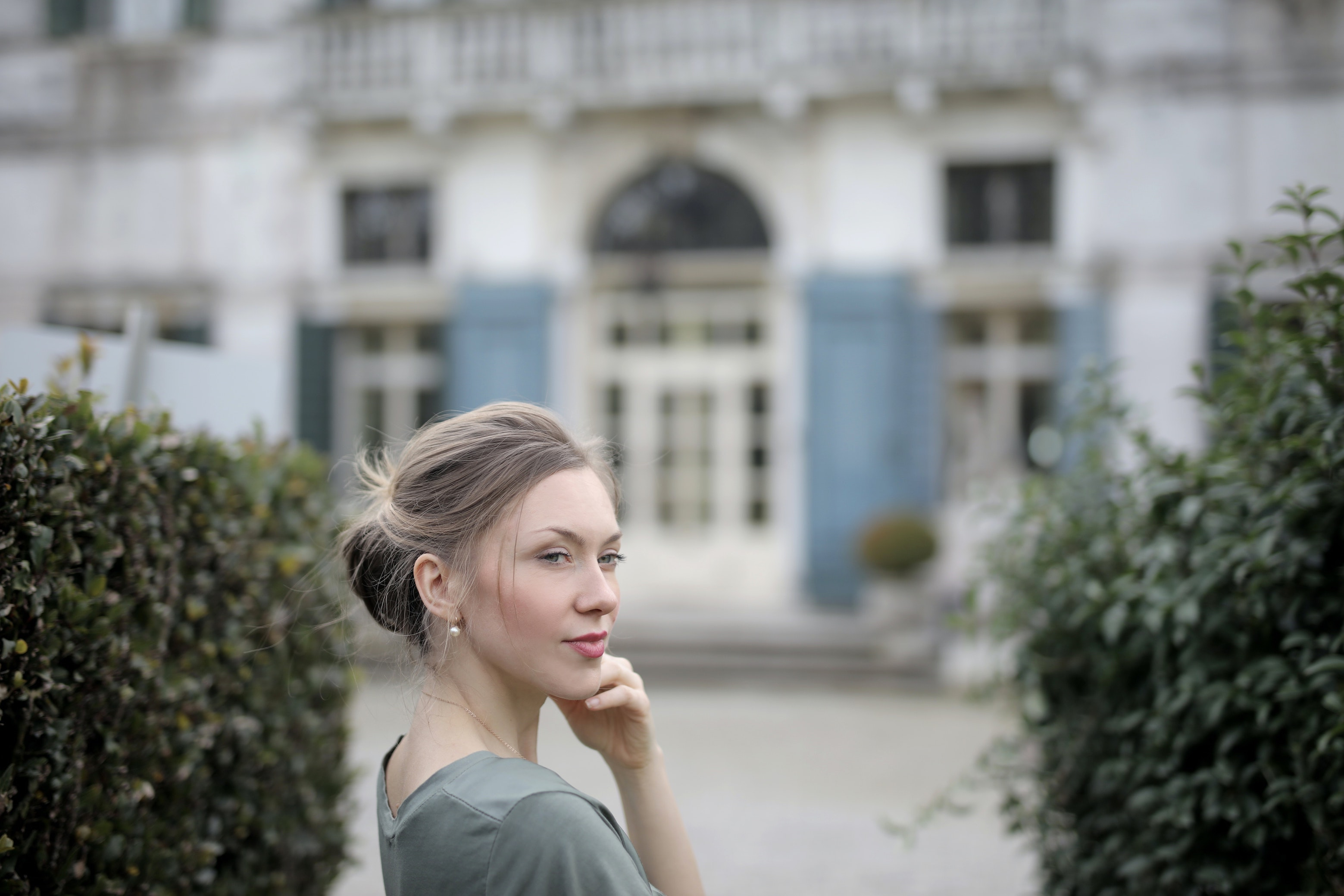 pensive-woman-on-background-of-old-palace-among-plants-3831034